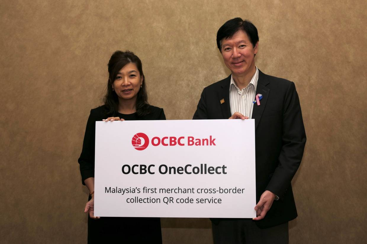 From left: Chong Lee Ying, managing director & head of global transaction banking, OCBC Bank (M) Bhd and Datuk Ong Eng Bin, the bank's CEO, introducing OCBC OneCollect, Malaysia's first merchant cross-border QR code collection service.  Credit: OCBC Bank